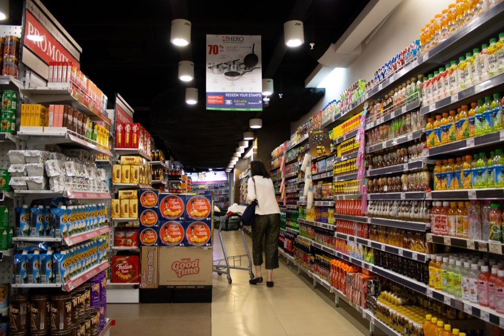 A masked customer moving through a food and beverage aisle in the supermarket